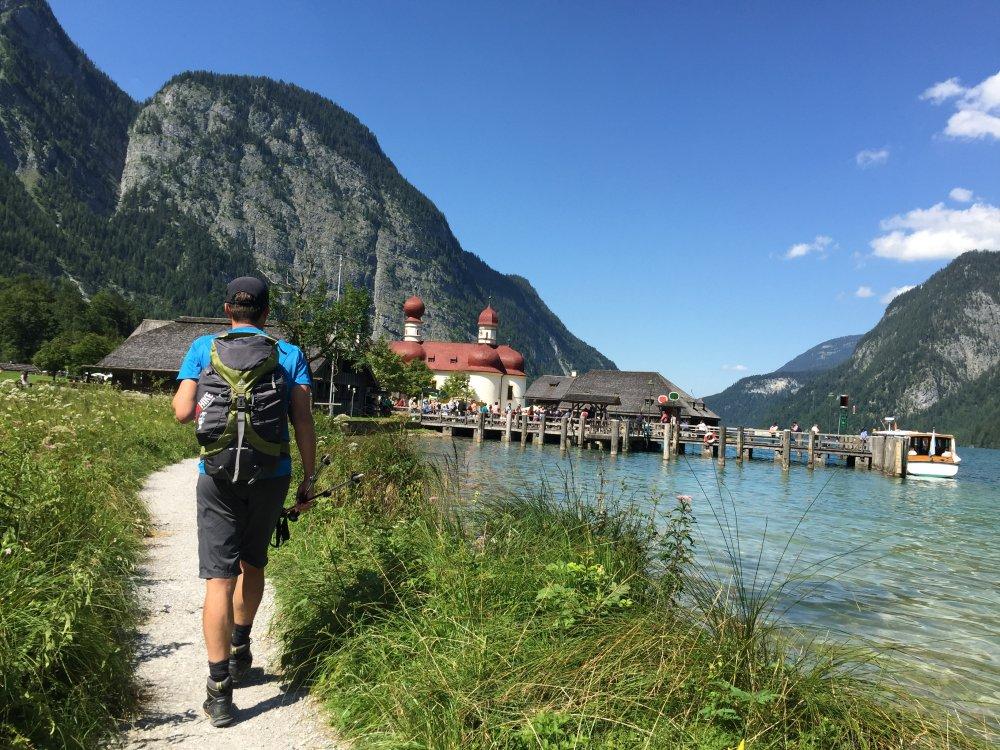 Wanderer am Königssee an der Wallfahrtskirche St. Bartholomä