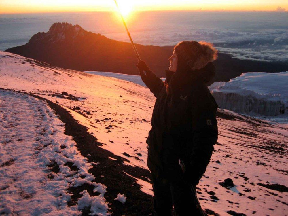 Bergsteigerin erlebt den Sonnenaufgang am Kilimanjaro