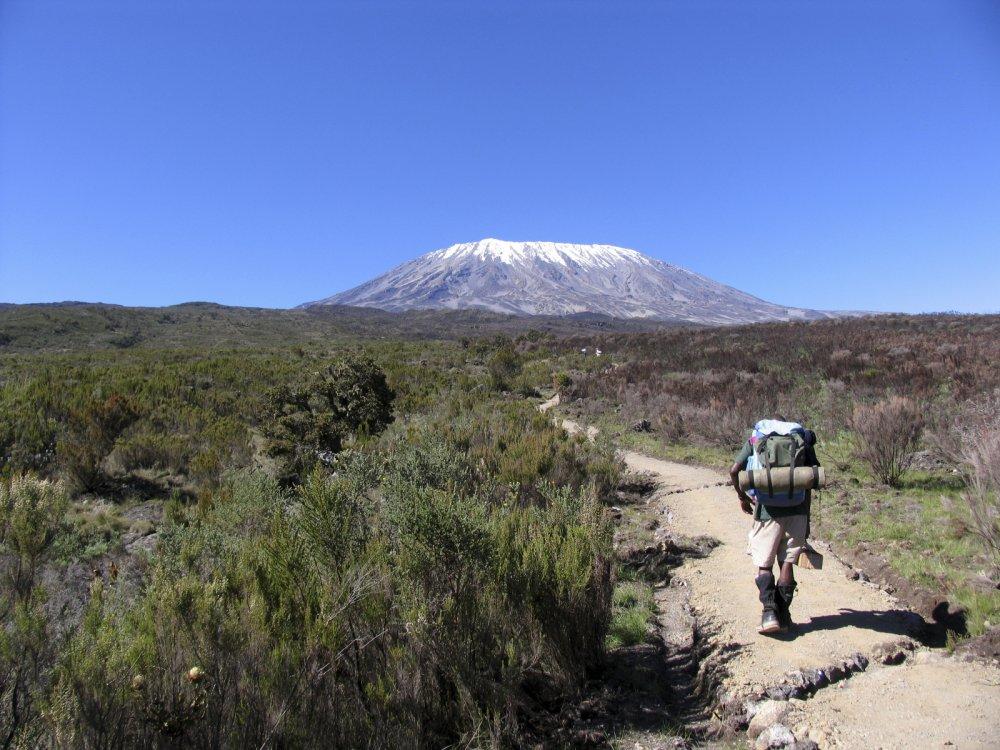Träger unterwegs auf der Marangu Route mit Blick auf den Gipfel der Kilimandscharo