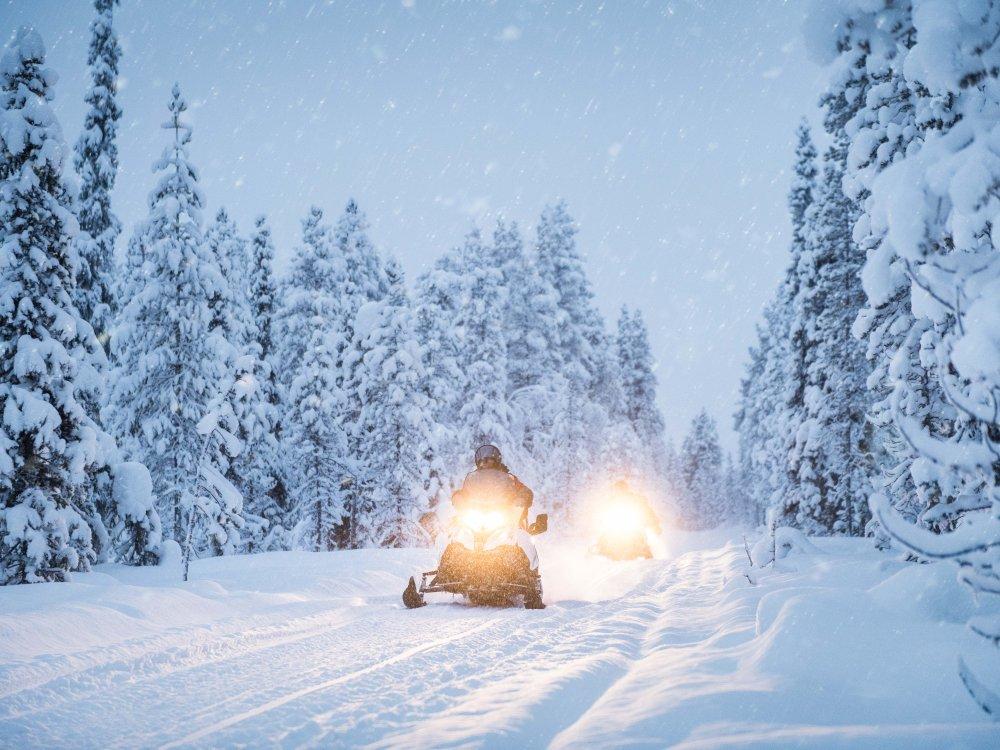 Schneemobil Tour durch den tief verschneiten Wald in Finnisch Lappland